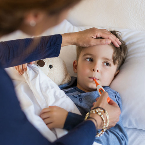 Child with a fever gets temperature taken