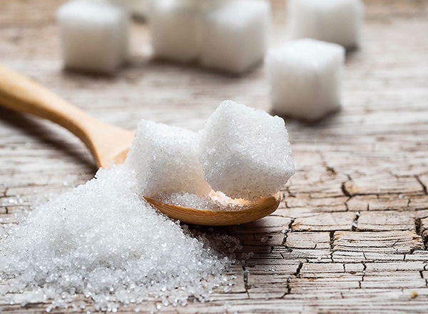 Added sugar on a spoon, stacked sugar cubes, diabetes